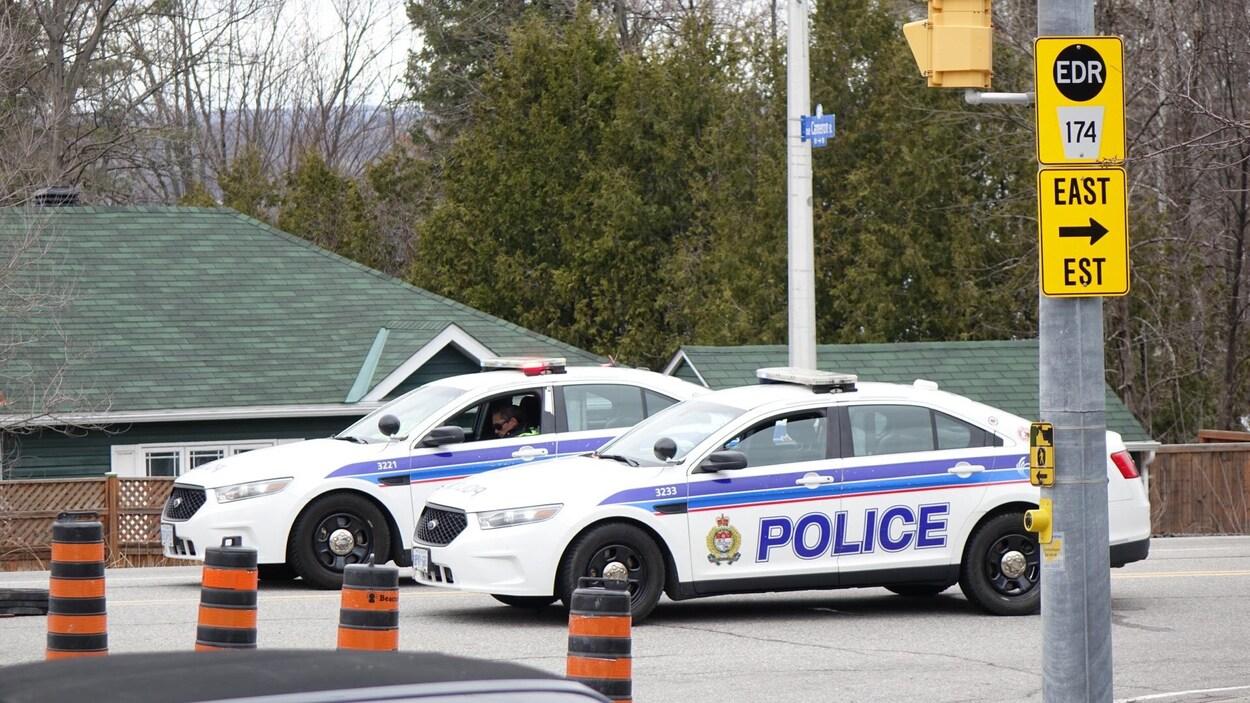 Deux auto-patrouilles du Service de police d'Ottawa bloquent une route.