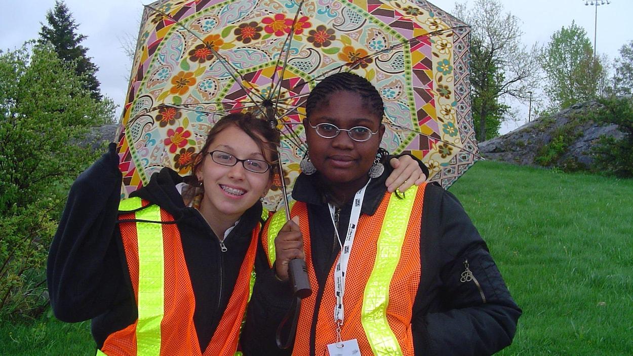 Les deux jeunes participantes portent un parapluie dehors. Elle porte un badge des jeux et un vêtement avec des rubans réfléchissants