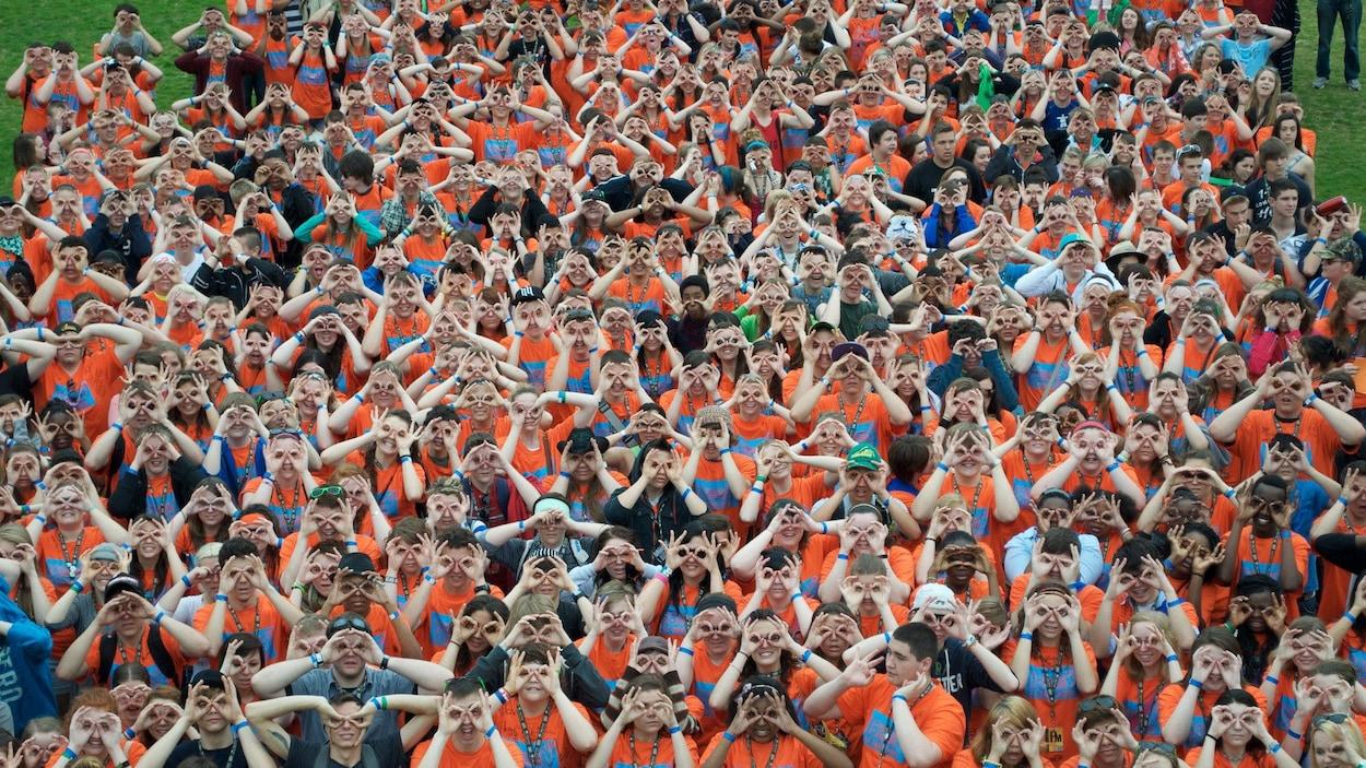 Une foule de jeunes gens qui miment des lunettes avec leurs doigts.