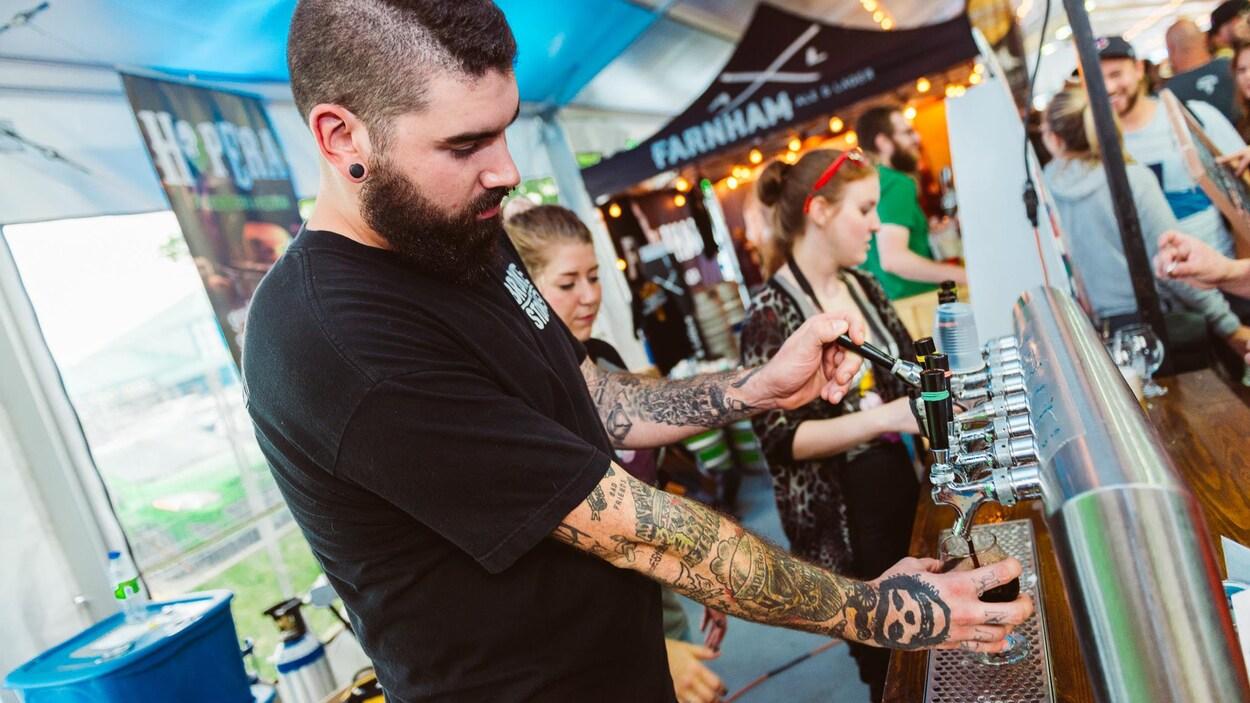 Un homme qui sert une bière dans un festival.