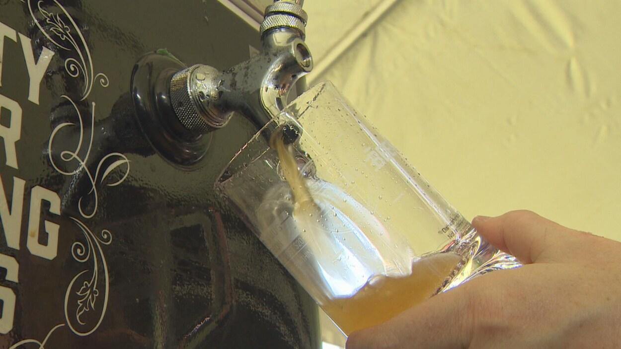 une main tient un verre qui est en train d'être rempli de bière