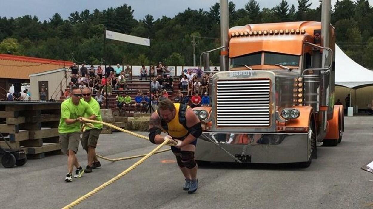 Photo de ld'un homme qui  tire un camion lourd à la compétition d'hommes forts de Plantagenet.