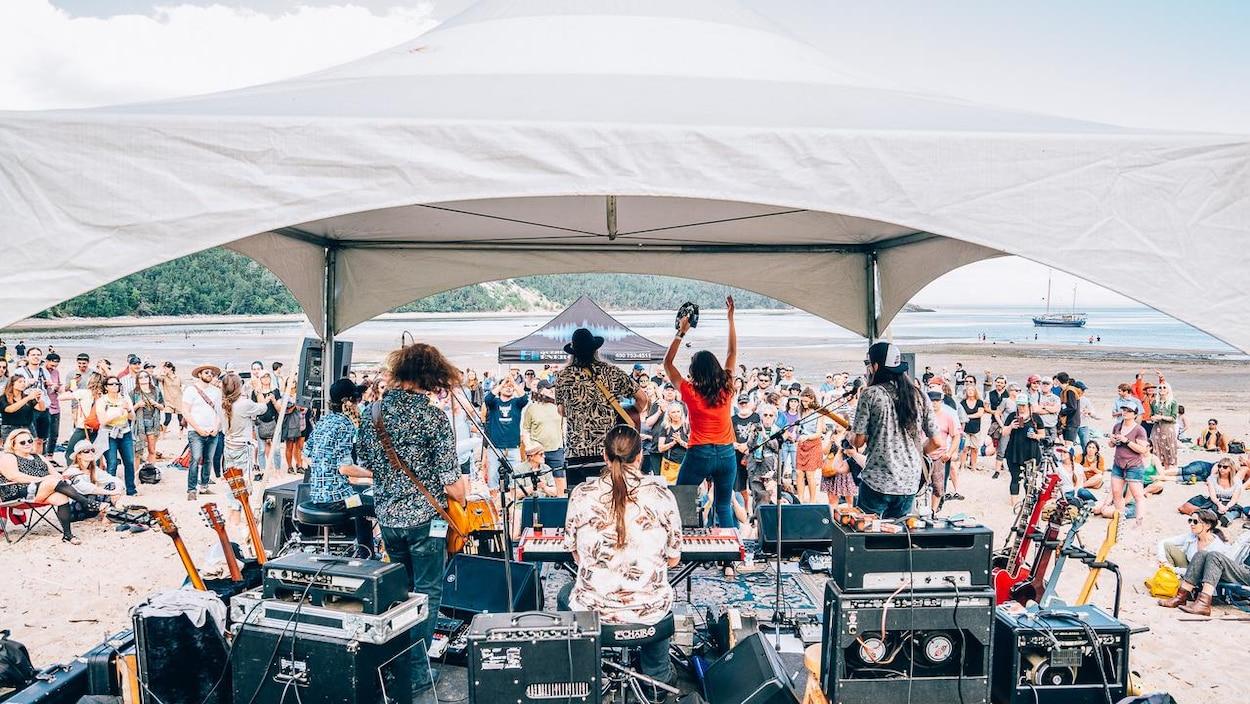 Un groupe de musique sur une scène sur la plage. Quelque centaines de festivalier les écoutent.