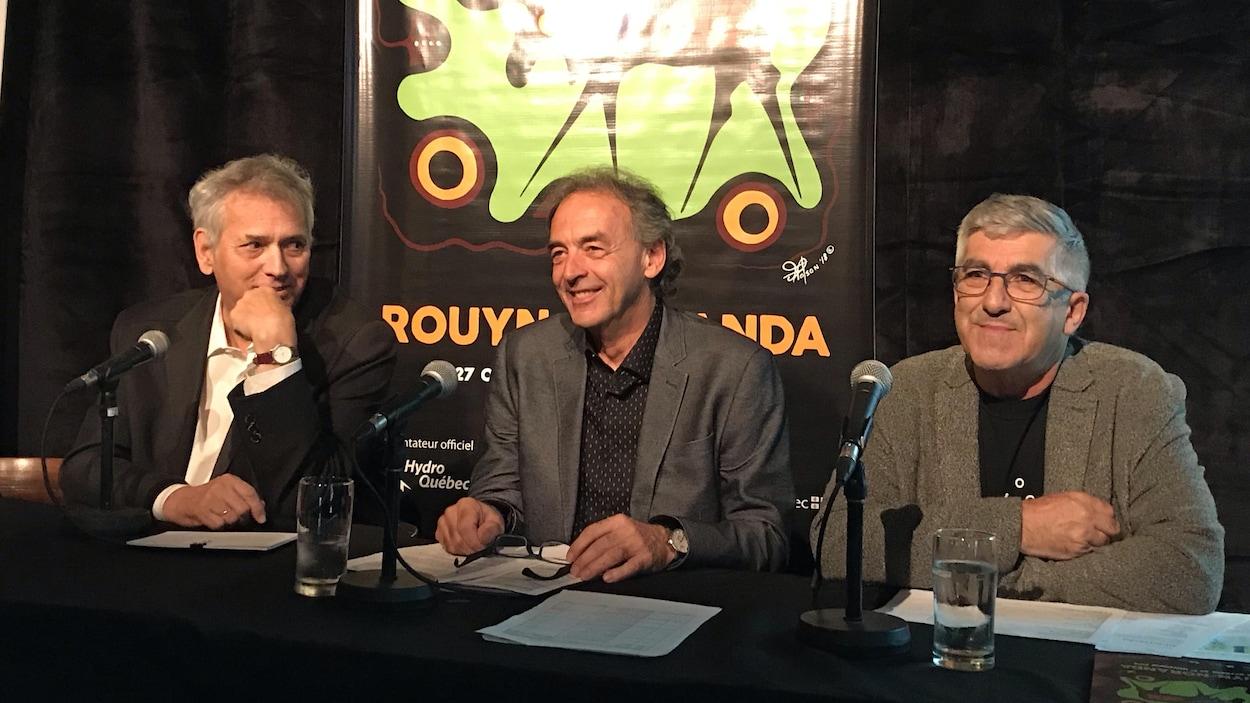 Trois hommes sont assis derrière une table durant une conférence de presse.