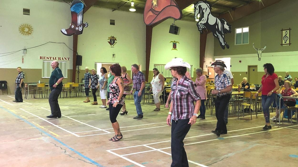 Des danseurs en ligne s'exercent dans un gymnase.
