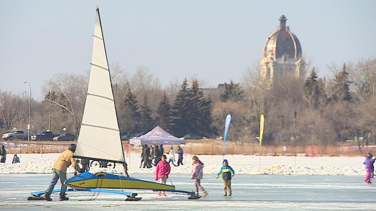 Des enfants jouent dehors dans le parc Waskana avec un voilier à glace.
