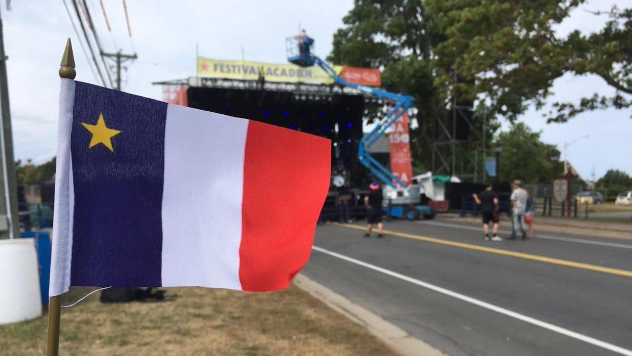 Un drapeau acadien devant une scène extérieure.