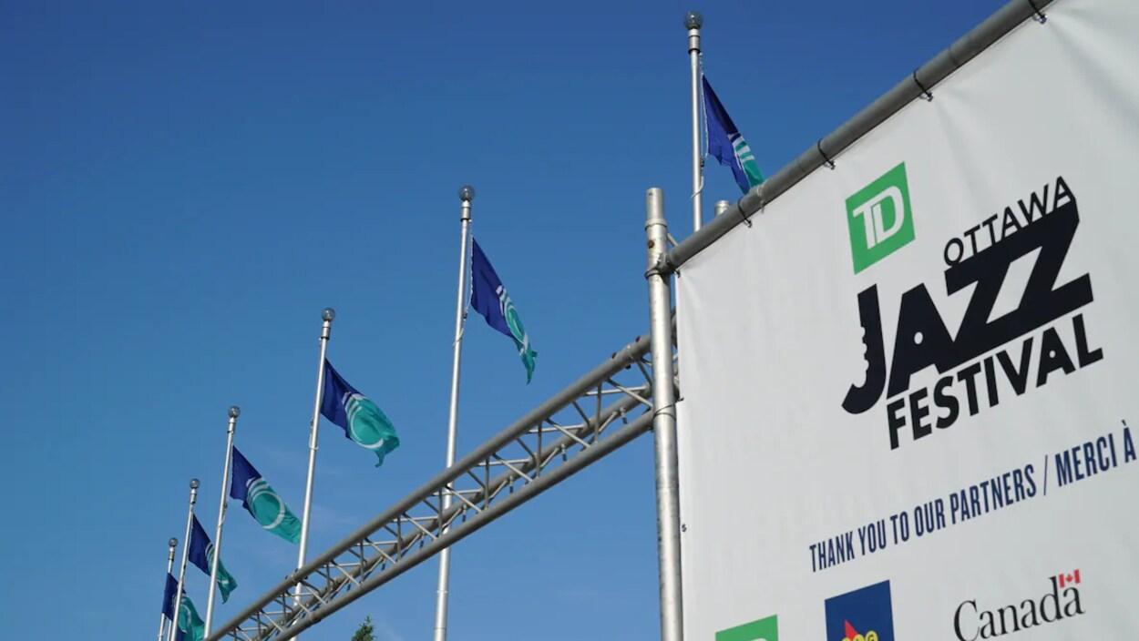 Une enseigne du Festival de jazz d'Ottawa avec, en arrière-plan, des drapeaux de la Ville d'Ottawa.