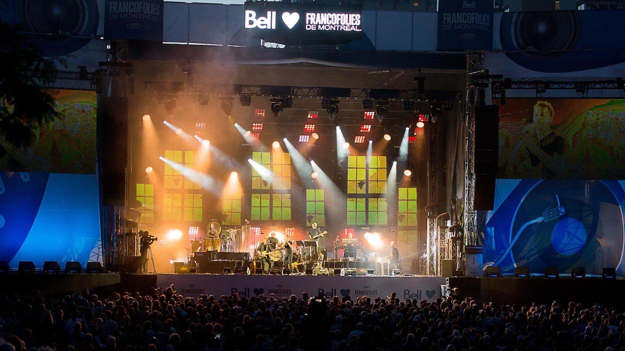 La foule est devant une scène avec des musiciens et des musiciennes.