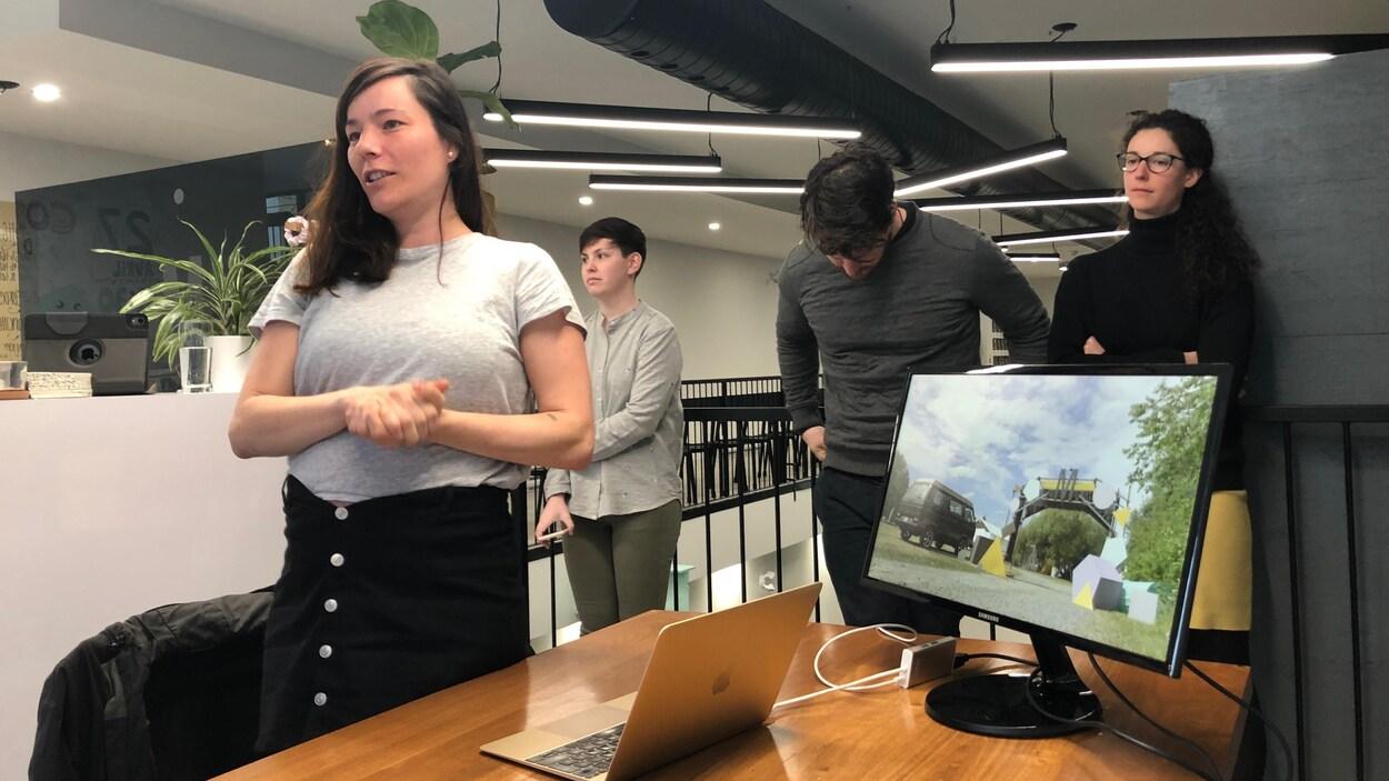 Une jeune femme parle lors d'une présentation, appuyée par une projection sur ordinateur.