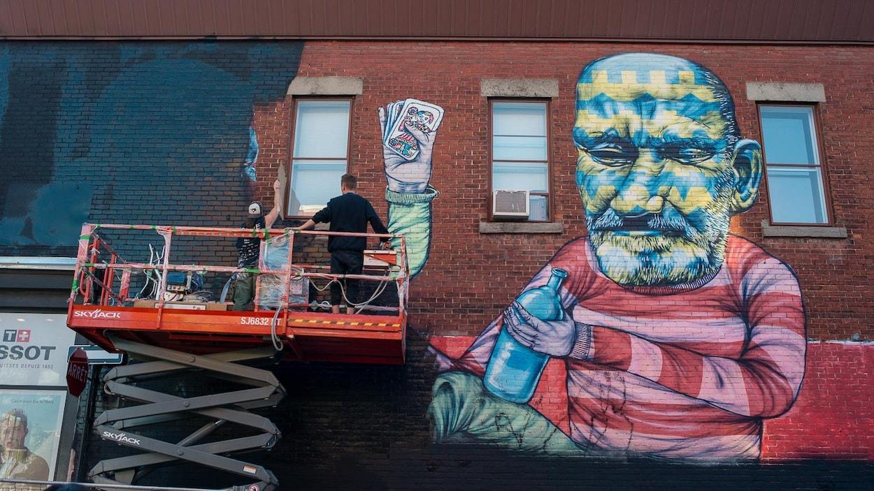 Deux personnes peignent de noir la mural de Other, réalisée en 2013.