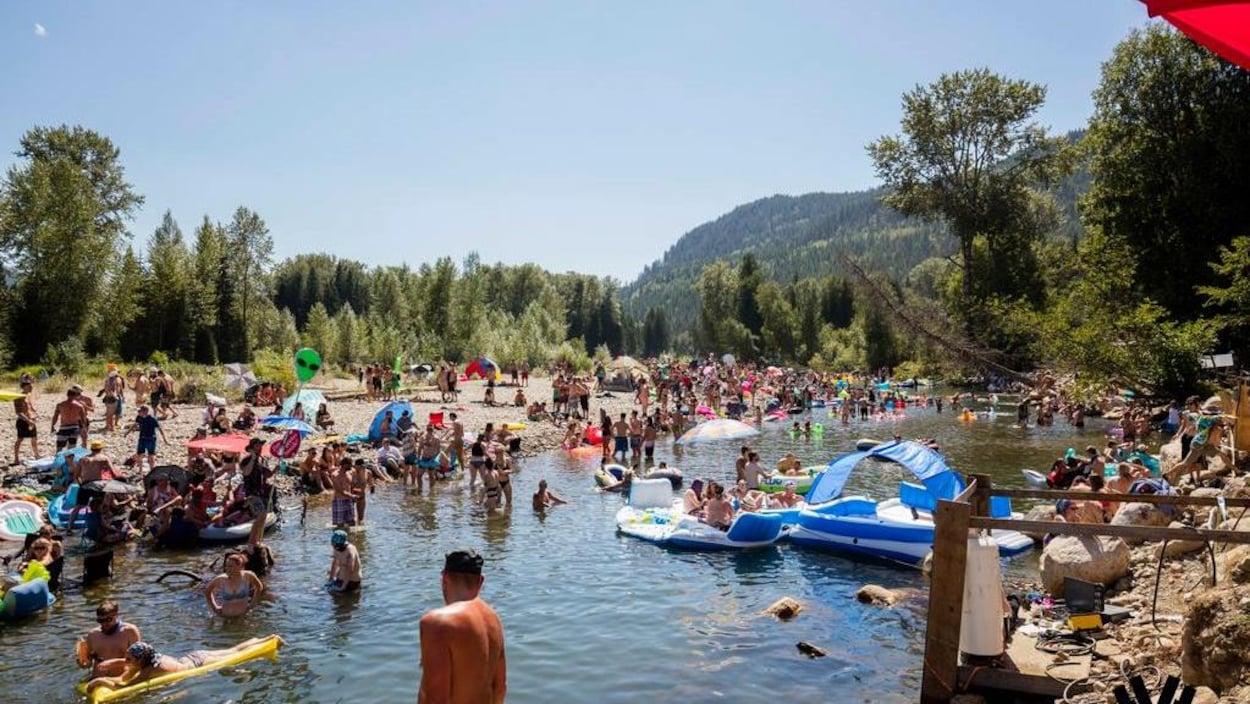 Des festivaliers du festival de musique électronique Shambhala se baignent dans l'eau