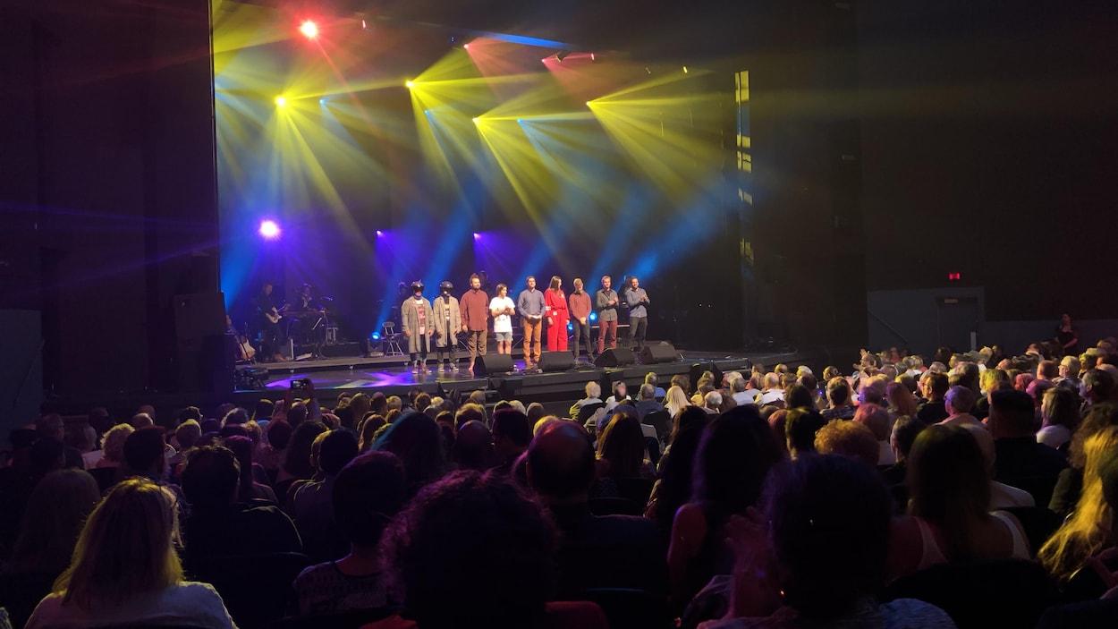 Les finalistes du 51e Festival international de la chanson de Granby, sur une scène extérieure devant une foule le soir.