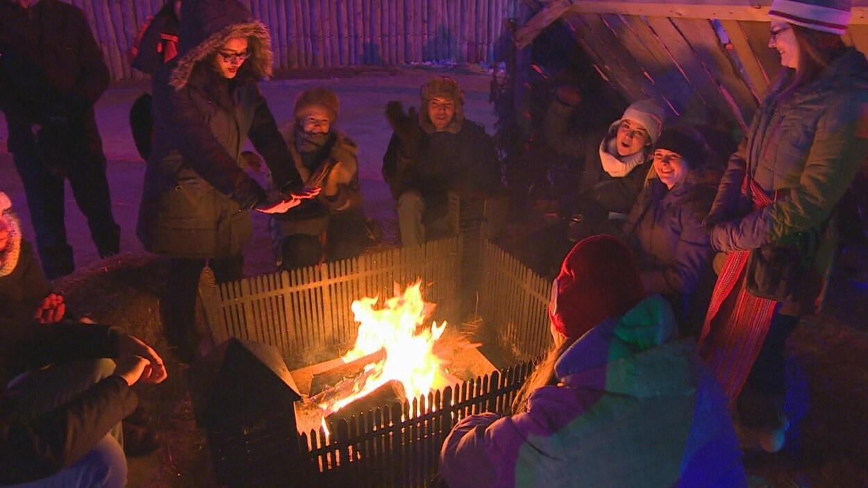 Des gens se réchauffent près d'un feu.