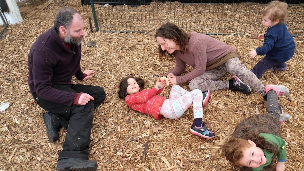Une famille de deux parents et trois petits enfants allongés sur le sol dans une tente du festival.