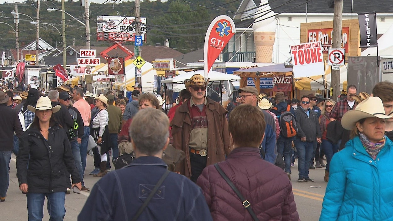 Une rue bondée de visiteurs portant des chapeaux de cowboy.