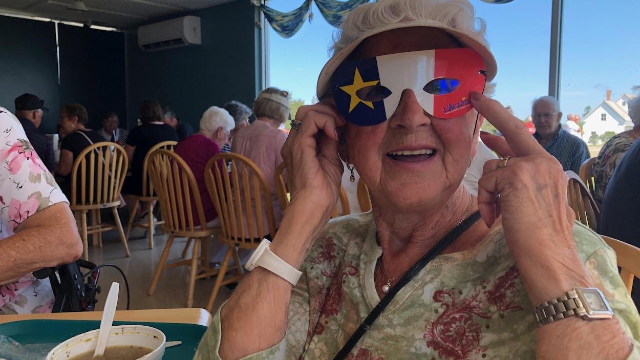 Une femme avec des lunettes en carton aux couleurs de l'Acadie.