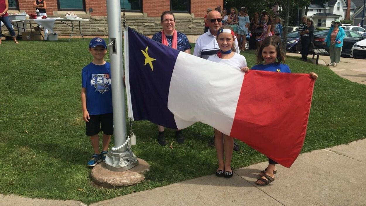 Groupe de personnes devant un drapeau acadien que l'on va hisser.