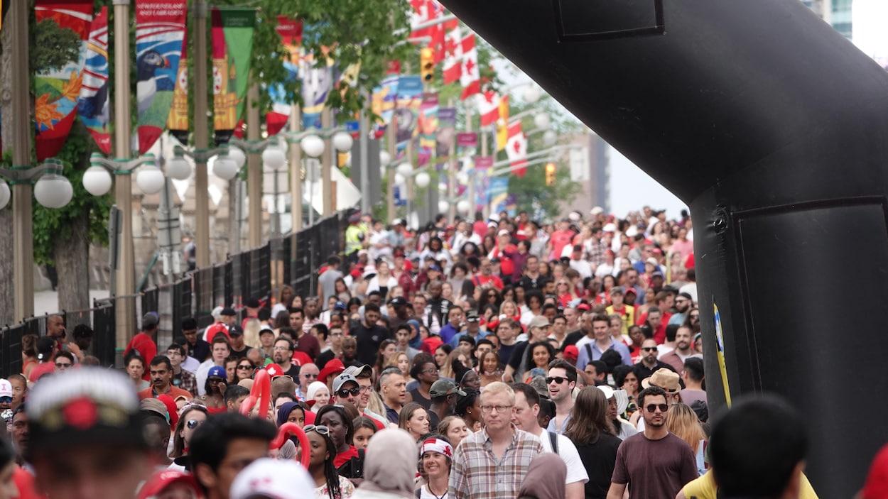 Une foule qui descend la rue Wellington à Ottawa sous une arche gonflable.
