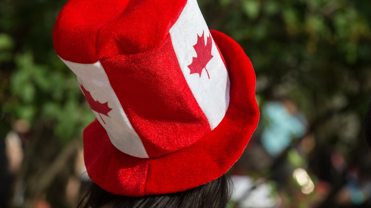 Une femme porte un chapeau aux couleurs du drapeau du Canada.