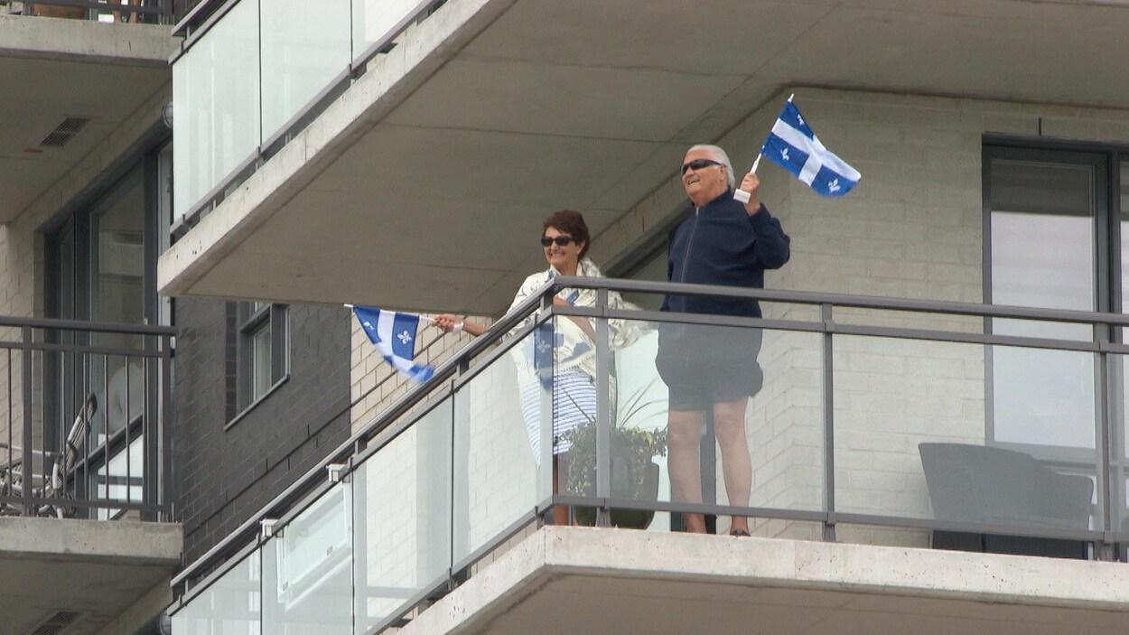 Un homme et une femme agitent chacun un drapeau du Québec sur leur balcon.