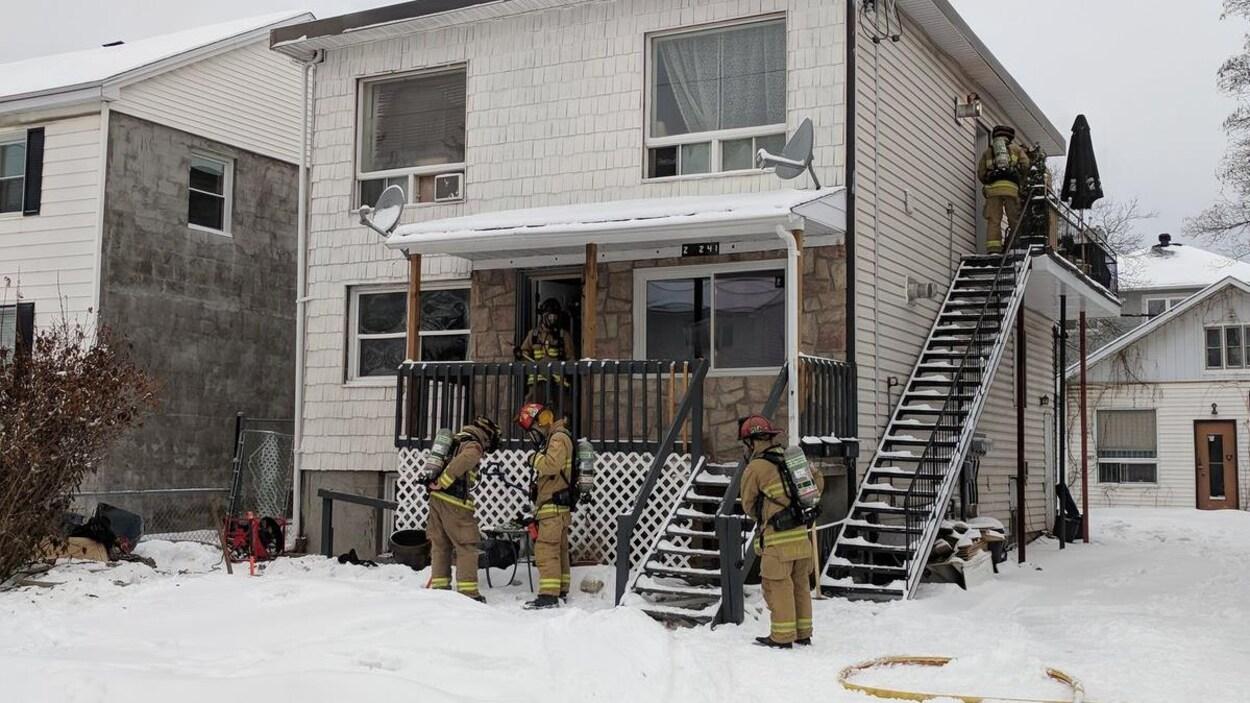 Une demi-douzaine de pompiers examinent la scène devant un immeuble de deux étages.