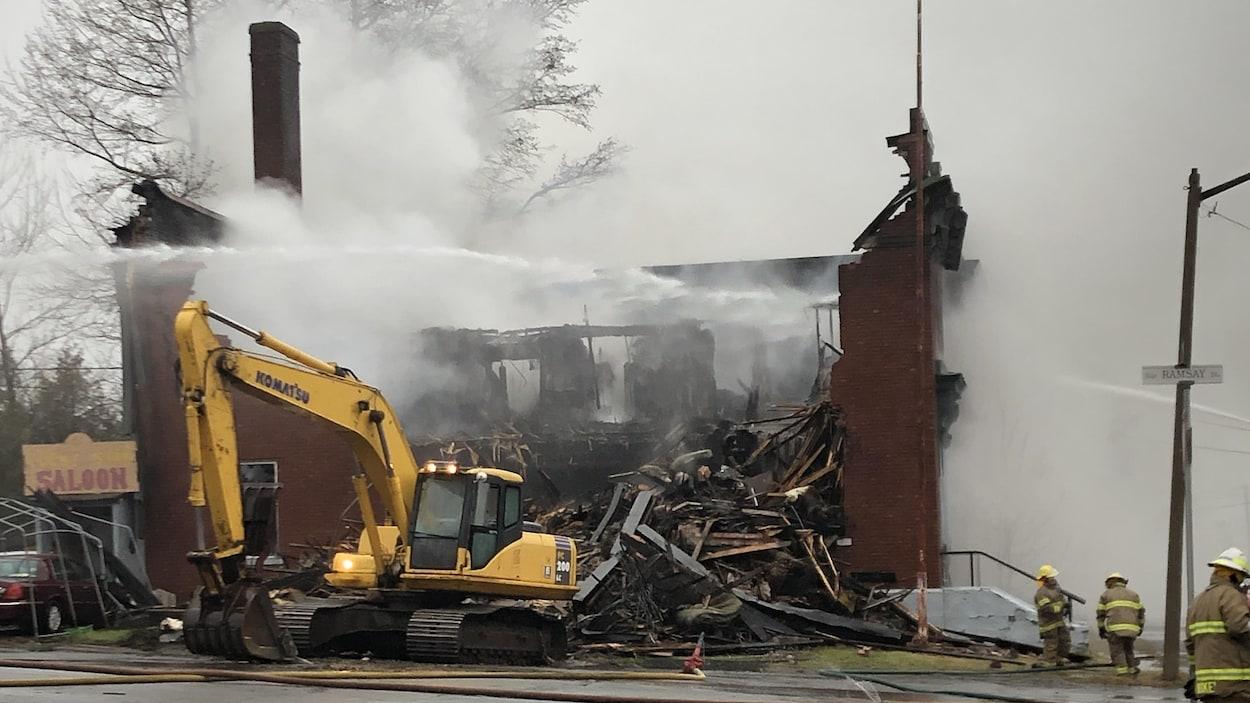 Édifice en briques rouges en feu et la structure est démolie.