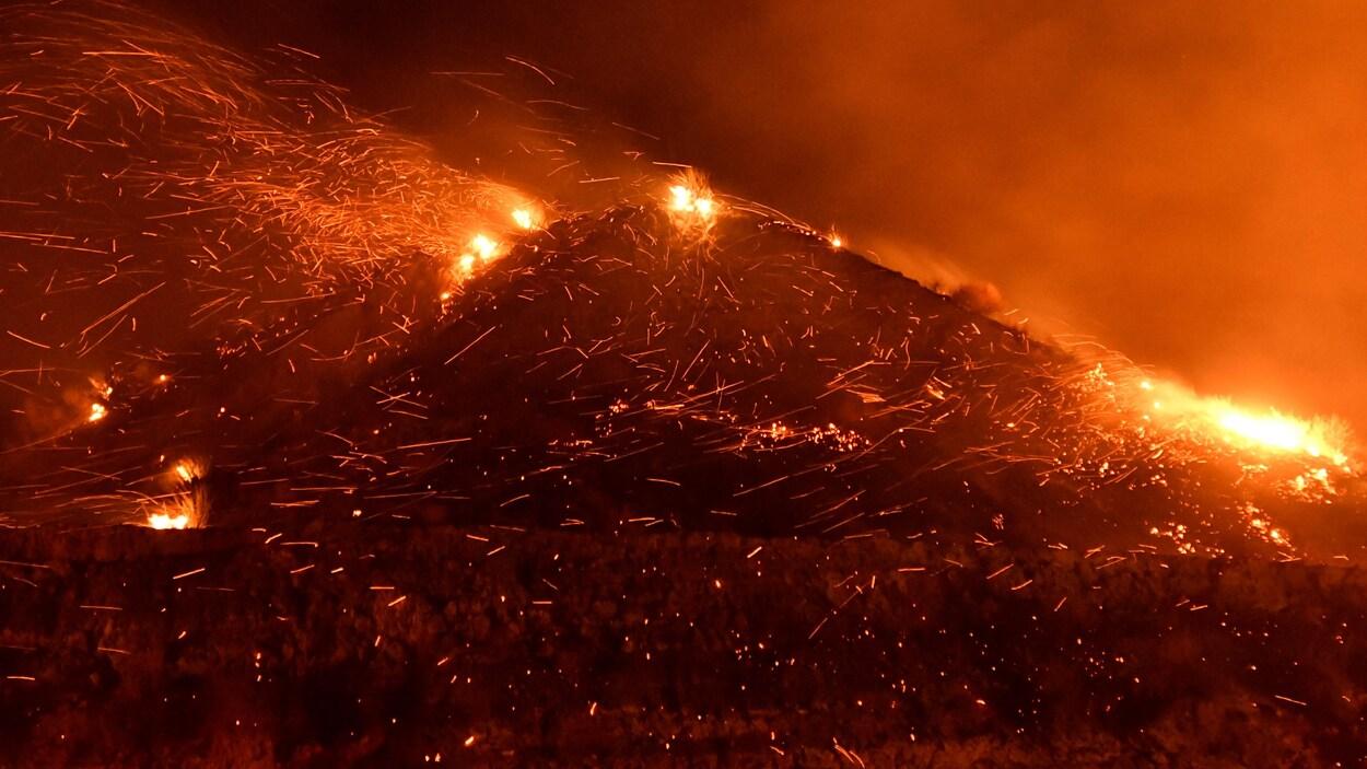 Dans la nuit, une montagne est ravagée par les flammes. Le vent souffle fort, faisant virevolter des tisons.