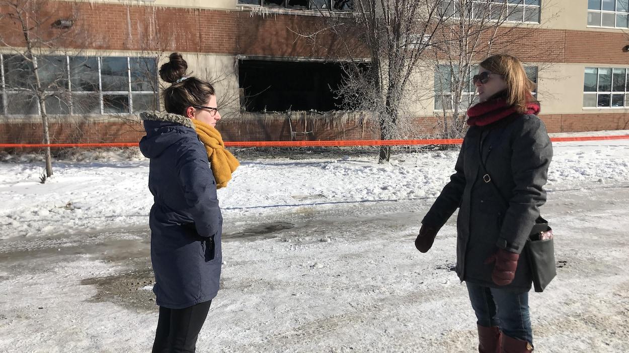 Deux femmes se font face devant un immeuble touché par un incendie.