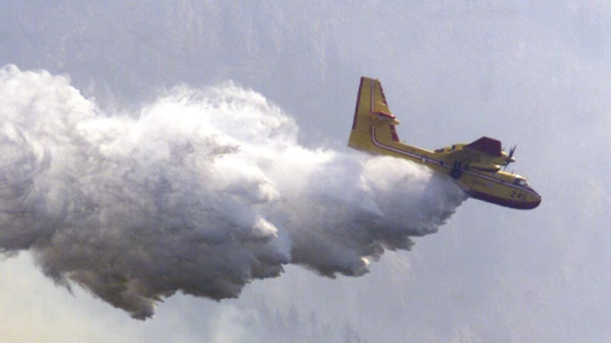 Un bombardier d'eau arrose un feu de forêt en Alberta.