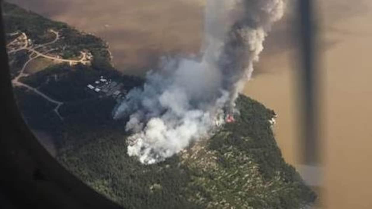 L'incendie Red Lake District Fire Number 066, près de la Première Nation de Sandy Lake, située dans le district de Kenora. Image prise d'un avion au dessus de la communauté. On y voit de la fumée près de bâtiments.
