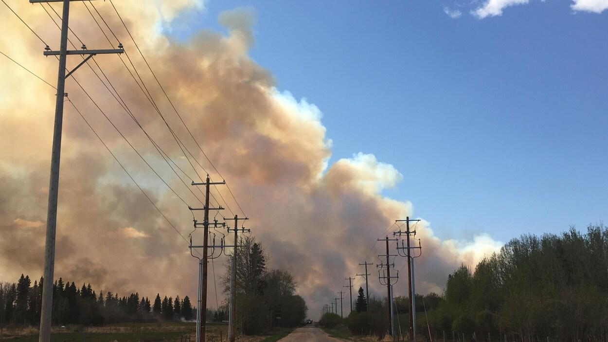 La route 562, dans le comté de Strathcona, avec, au loin, un épais panache de fumée qui recouvre la majeure partie du ciel.