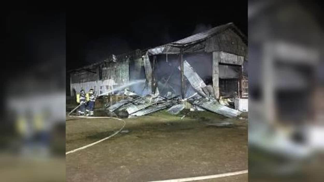 Deux pompiers arrosent une grange qui a été détruite par les flammes.
