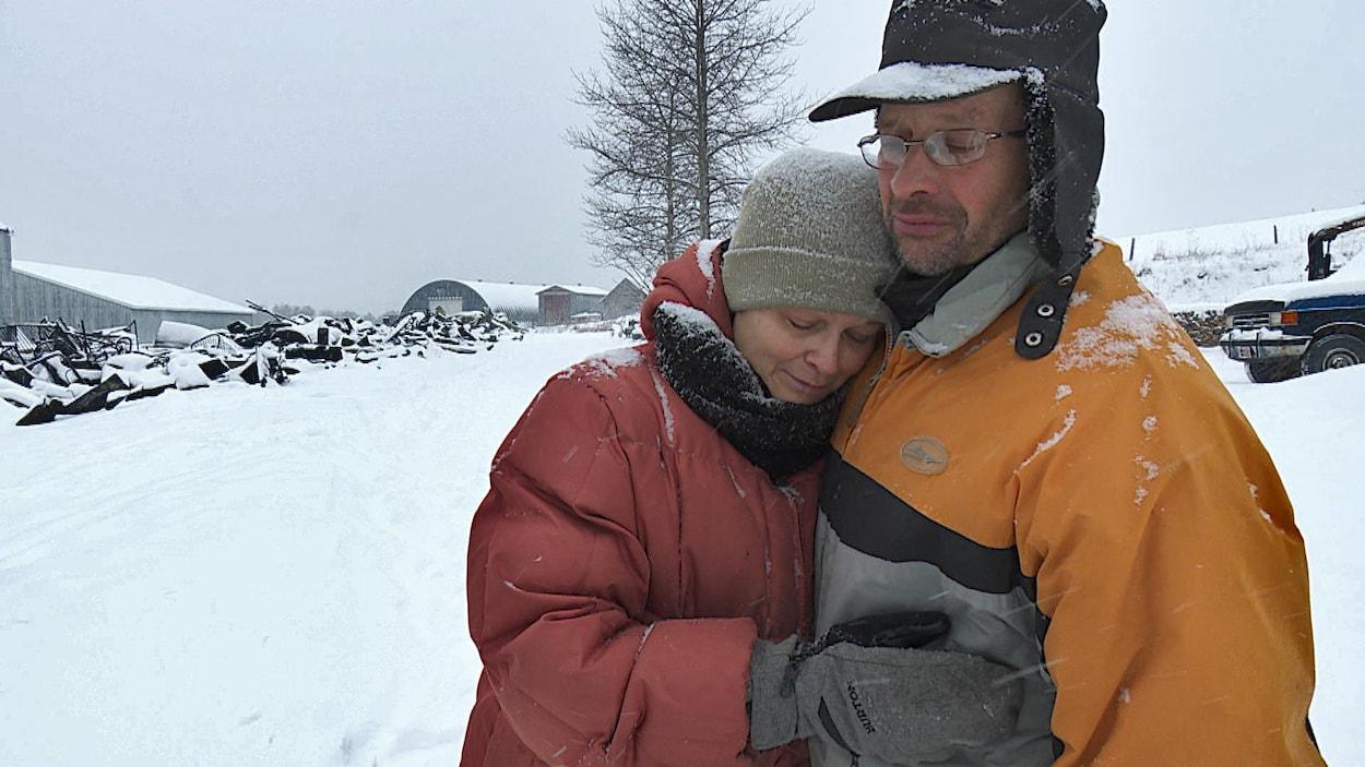 Le couple se serre dans ses bras près des ruines enneigées.