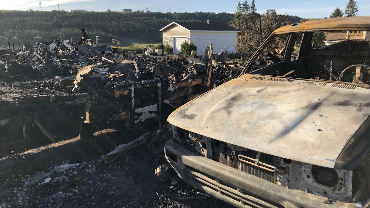 Une voiture calcinée devant une maison en cendres.