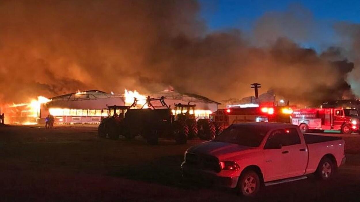 Le feu consume l'étable alors que les pompiers sont à l'œuvre.