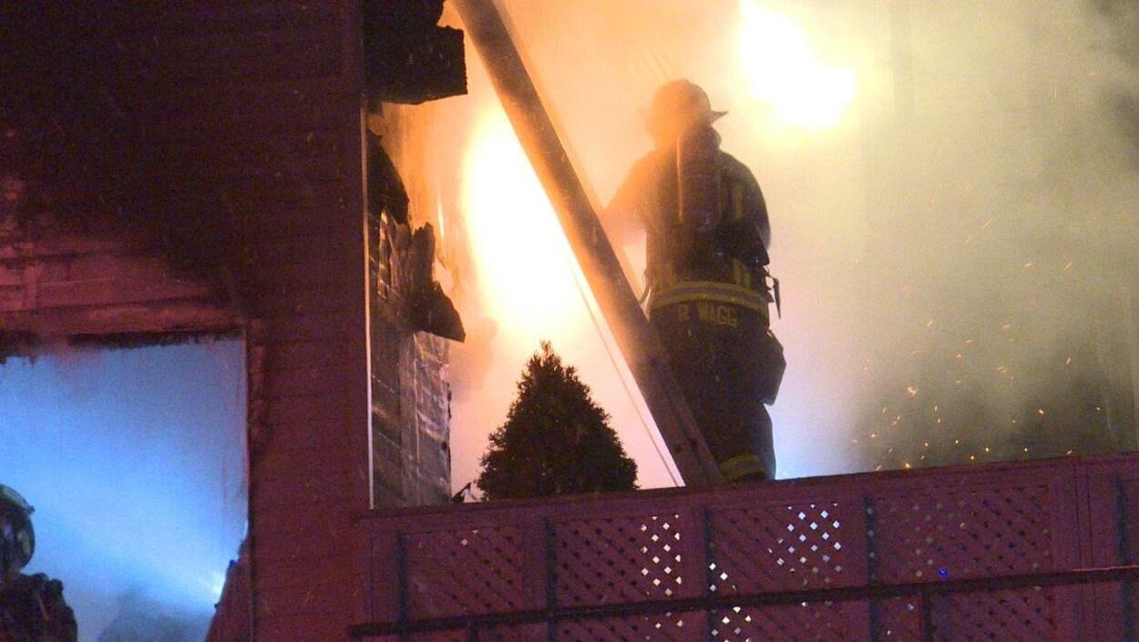 Photo d'un pompier qui se tient dans une échelle.