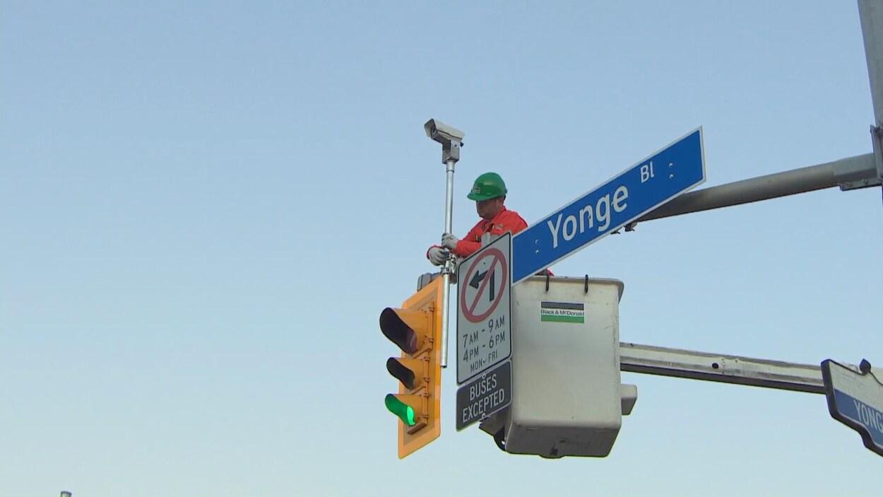 Un travailleur installe une caméra au-dessus d'un feu de circulation.