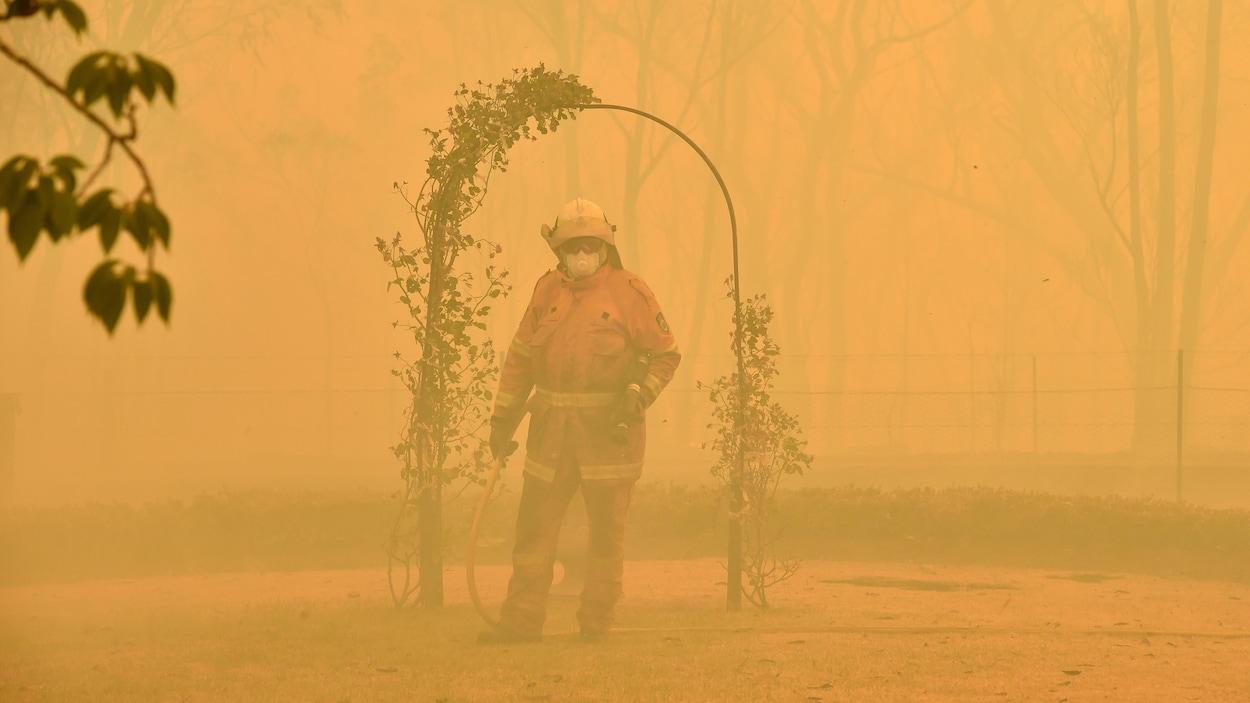 Un pompier combat un feu de forêt, encerclé par de la fumée.