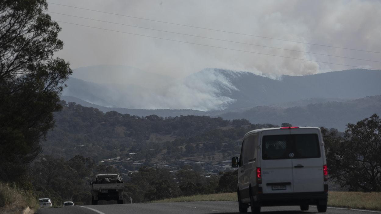 Une route avec, en arrière plan, des collines forestières d'où s'élève un panache de fumée.