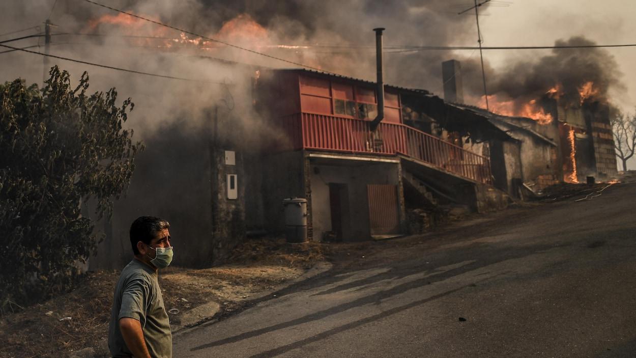 Un homme porte un masque pour se protéger de la fumée, alors que non loin de lui des édifices sont en flammes.