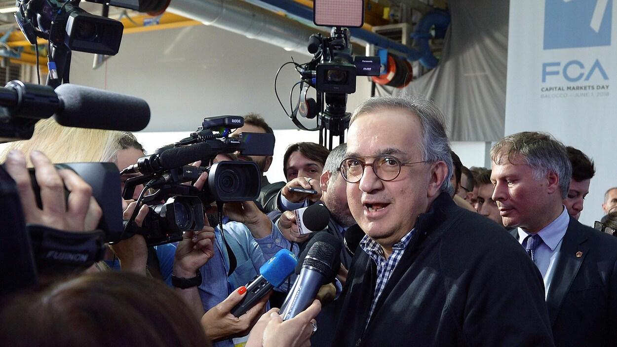 Un homme devant les caméras et les micros des journalistes.