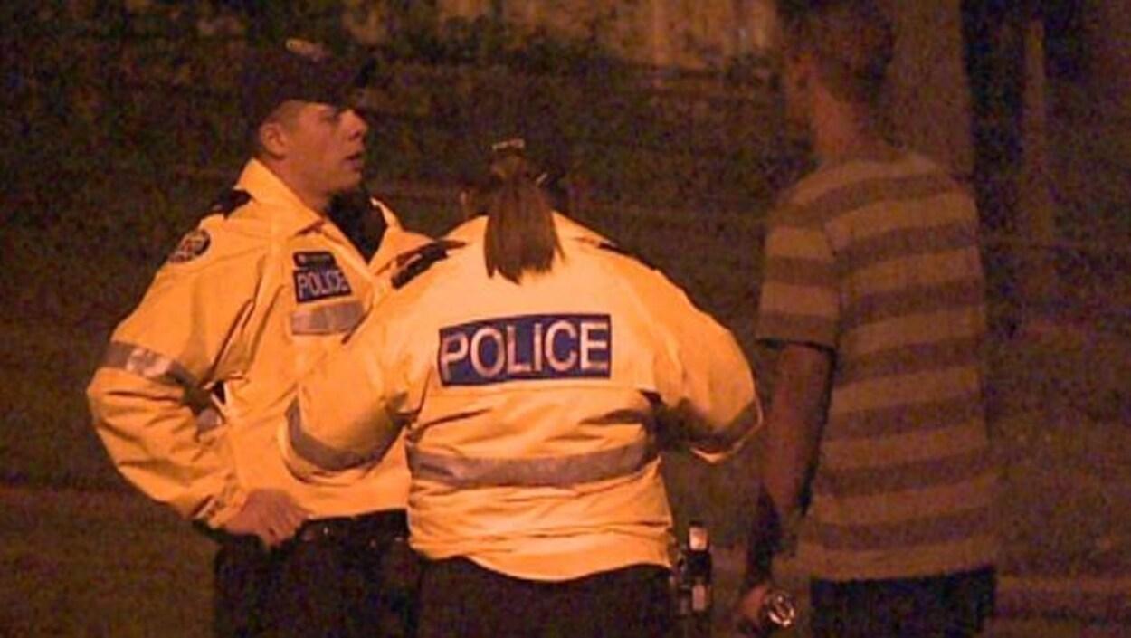 Photo de deux policiers qui interrogent un homme dans la rue.