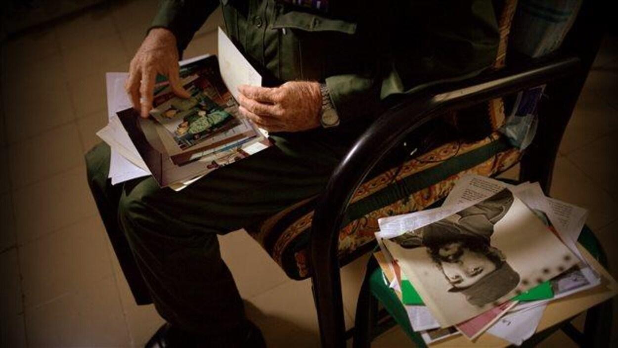 Personne assise consultant des photos et des souvenirs de Fidel Castro.
