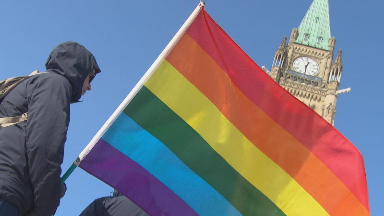 Un homme porte le drapeau de la Fierté. Derrière, on peut apercevoir la tour centrale du Parlement.
