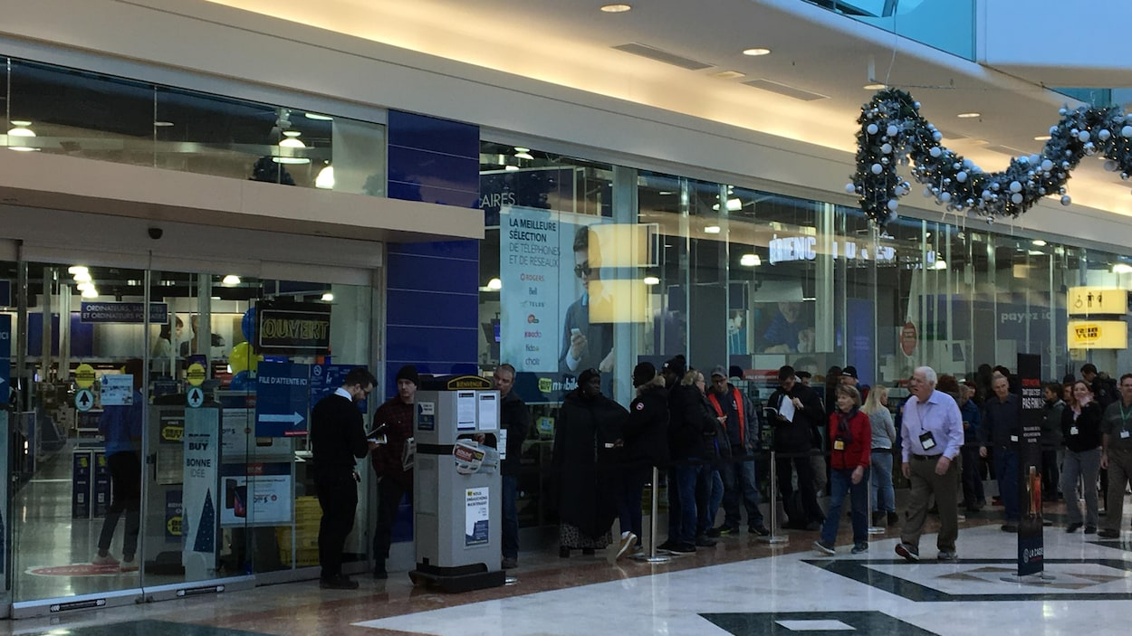 Des clients attendent en file l'ouverture du magasin Best Buy