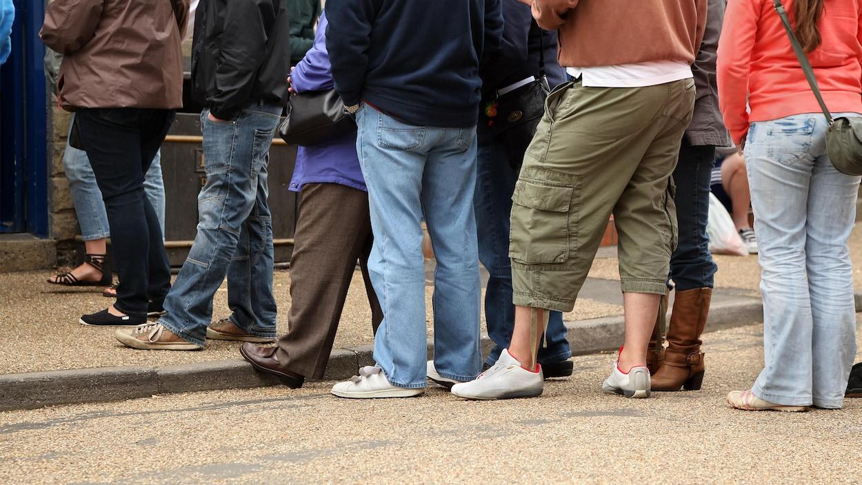 Des gens dont on ne voit pas le visage font la queue pour commander à un restaurant.