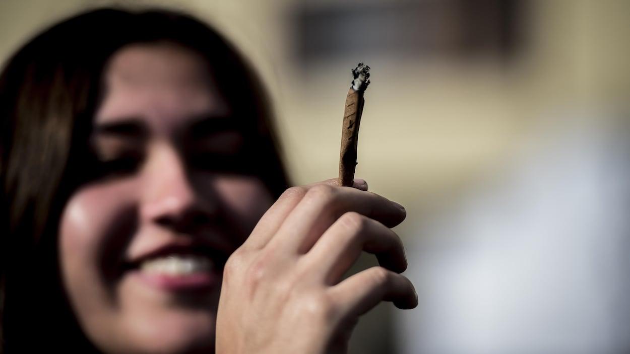 Une jeune fille souriante tient un joint dans sa main.
