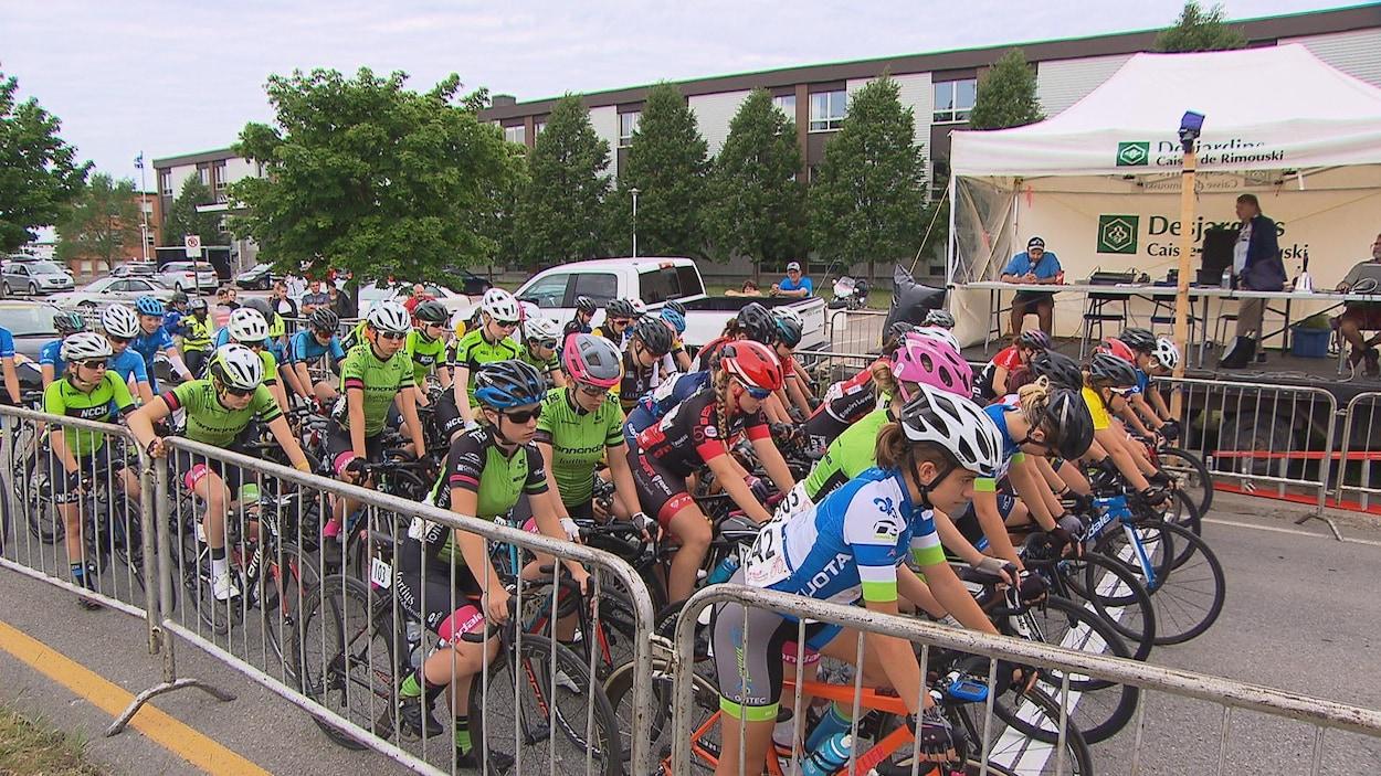 Des jeunes cyclistes féminines attendent sur la ligne de départ.