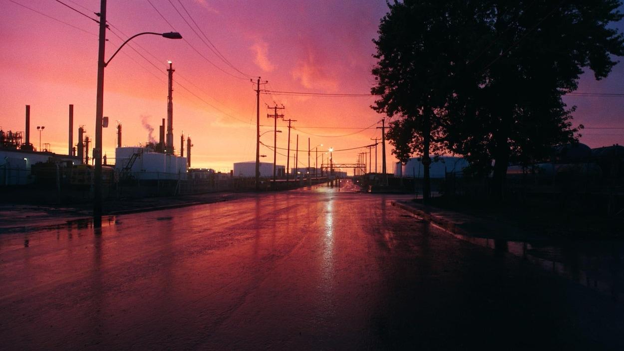 Le ciel rose se reflète sur une rue mouillée.